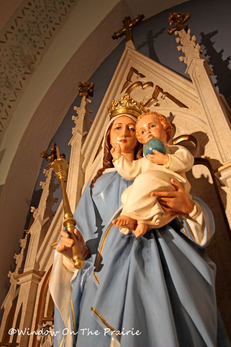statue of Mary holding the Baby Jesus on left side altar